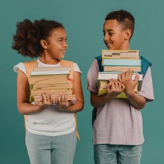 Niños sosteniendo montones de libros.