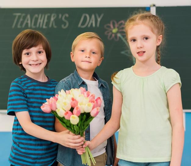 Niños sosteniendo un ramo de flores para su maestra.