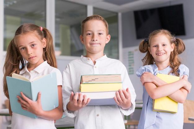 Niños sosteniendo sus libros en el aula.