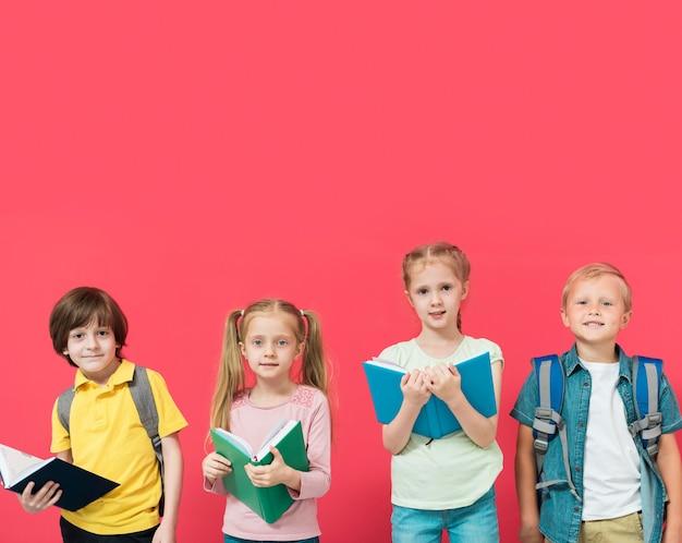 Niños sosteniendo sus libros con fondo rojo.