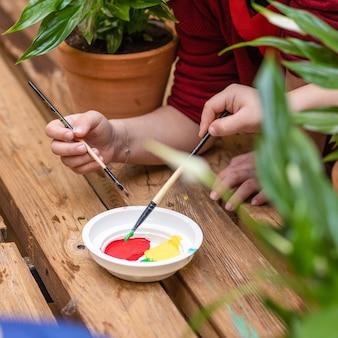 Niños sumergiendo la placa de pintura con una vista superior del cepillo