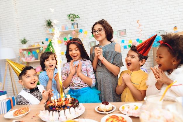 Niños con tarta y velas en ocasión de cumpleaños.