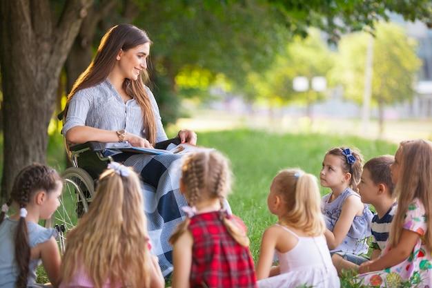 Los niños tienen una lección con el profesor en el parque en un césped verde.