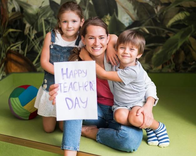 Niños de tiro completo abrazando profesor feliz
