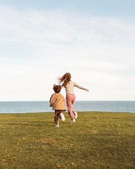 Niños de tiro completo corriendo al aire libre