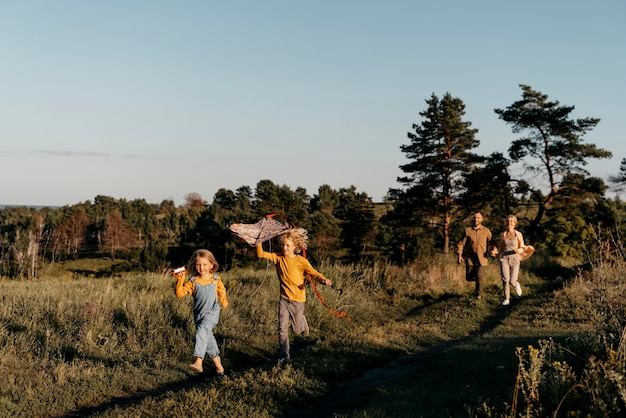 Niños de tiro completo jugando con cometa en la naturaleza