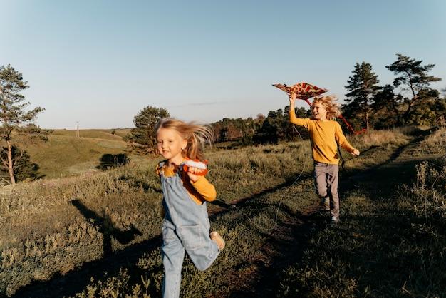 Niños de tiro completo jugando con cometa