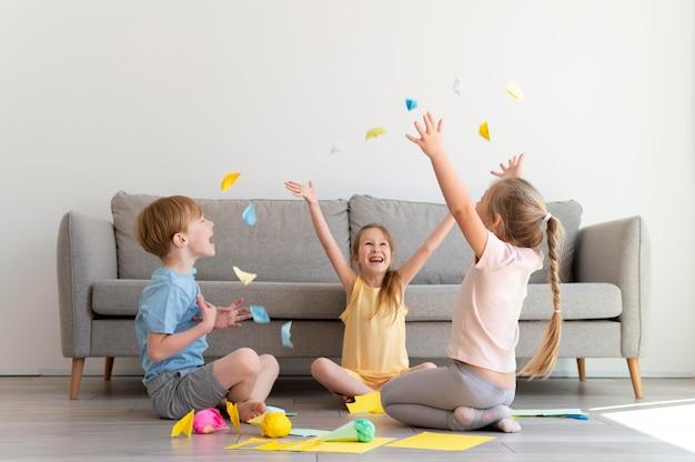 Niños de tiro completo jugando con papel