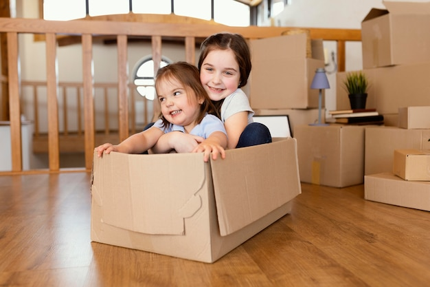 Niños de tiro completo sentados en caja