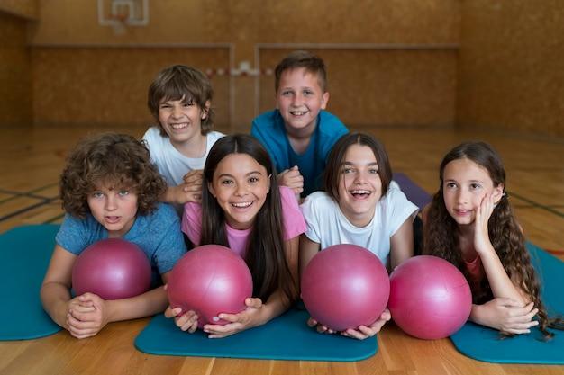 Niños de tiro completo tendido sobre colchonetas de yoga