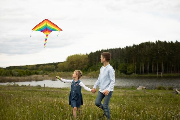Niños de tiro completo volando una cometa afuera