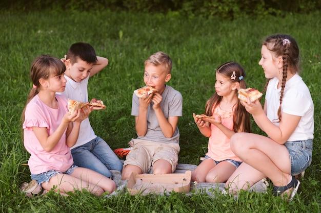 Niños de tiro largo comiendo una rebanada de pizza