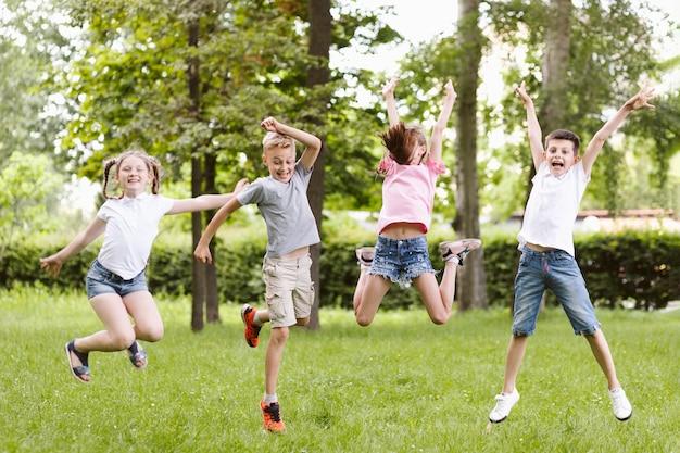 Niños de tiro largo saltando juntos