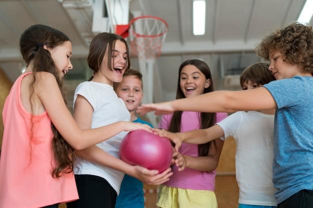 Niños de tiro medio con bola rosa
