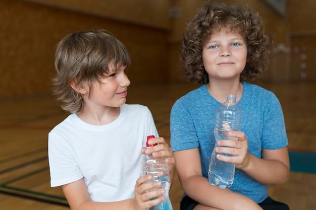 Niños de tiro medio con botellas de agua