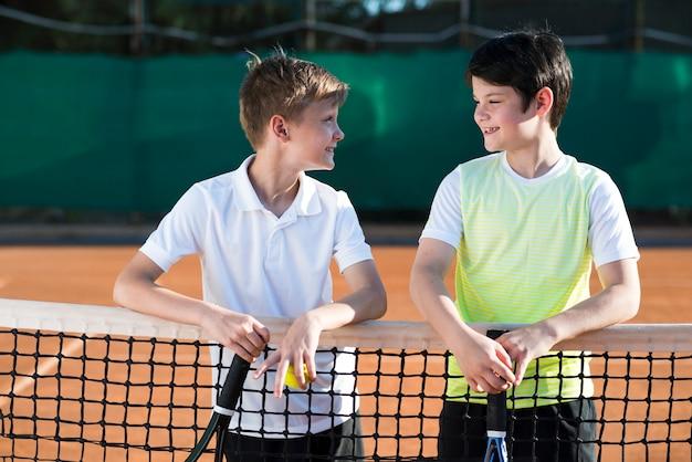 Niños de tiro medio en el campo de tenis.