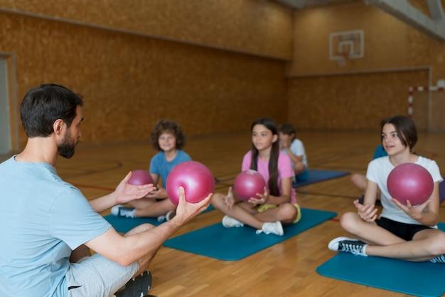Niños de tiro medio en colchonetas de yoga con bolas de color rosa