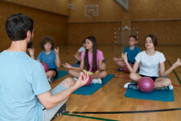 Niños de tiro medio en colchonetas de yoga en el gimnasio