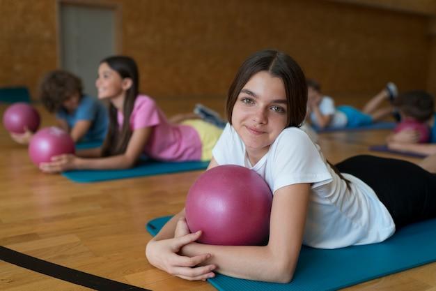 Niños de tiro medio en colchonetas de yoga con pelotas