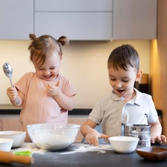 Niños de tiro medio divirtiéndose cocinando