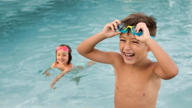 Niños de tiro medio divirtiéndose en la piscina