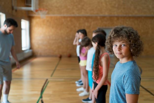Niños de tiro medio en el gimnasio de la escuela