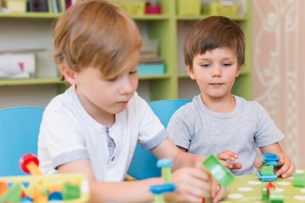 Niños de tiro medio jugando con juguetes