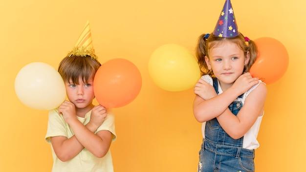 Niños de tiro medio sosteniendo globos
