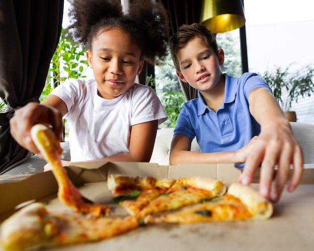 Niños de tiro medio sosteniendo porciones de pizza
