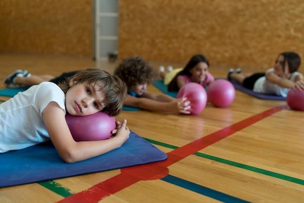 Niños de tiro medio tendido sobre colchonetas de yoga