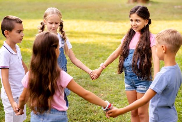 Niños tomados de la mano forman un círculo