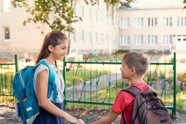 Niños tomados de la mano en el patio de la escuela.
