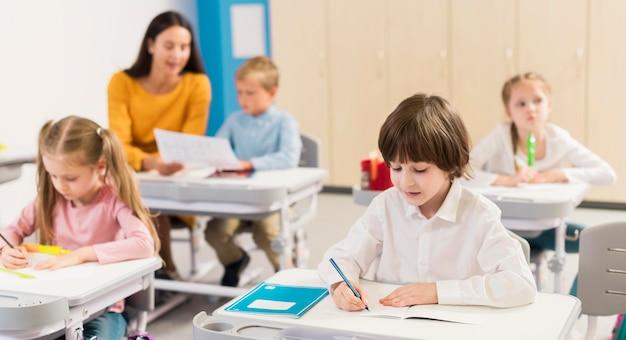 Niños tomando notas en clase.
