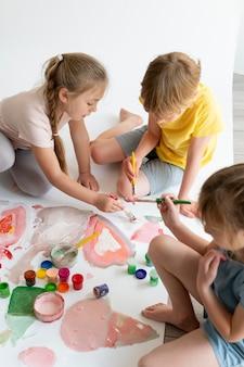 Niños de trabajo en equipo de cerca pintando juntos