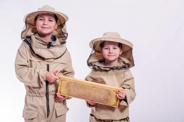 Niños en trajes de apicultor posando en blanco.