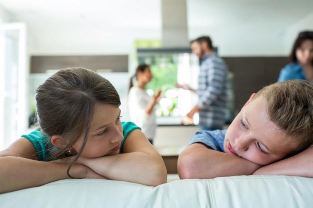 Niños tristes apoyándose en el sofá mientras los padres discuten