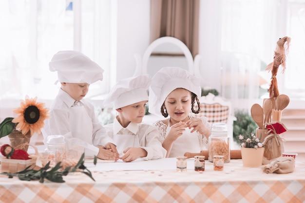 Niños en uniforme de chef cocinan postre.