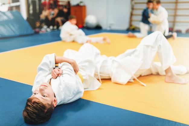Niños en uniforme, entrenamiento de judo para niños. jóvenes luchadores en gimnasio, arte marcial para la defensa