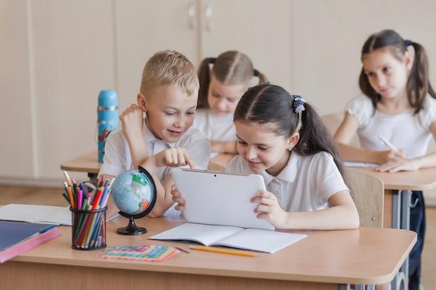 Niños usando tableta durante la lección