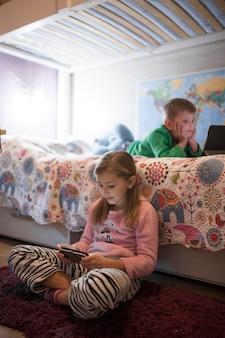 Niños usando tecnologías en el dormitorio