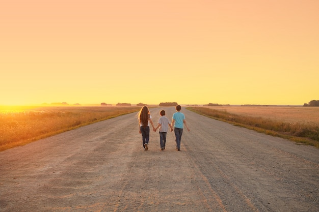 Los niños van por el camino para encontrarse con la puesta de sol.