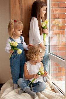 Niños en la ventana con flores.