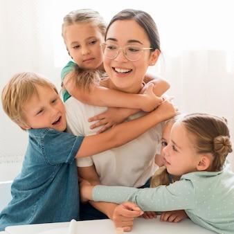 Niños de vista frontal abrazando a su maestro