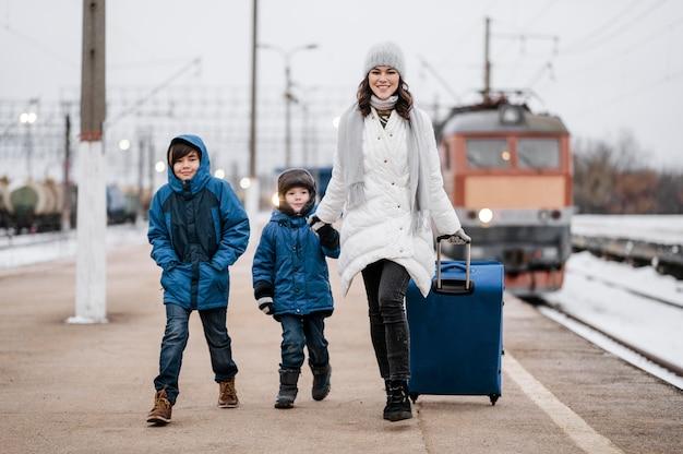 Niños de vista frontal y mujer en la estación de tren