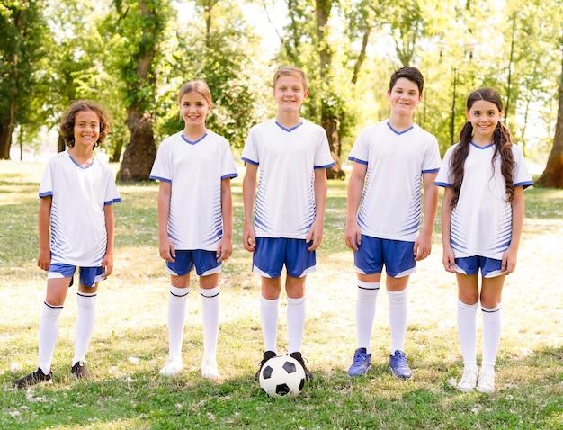 Niños de vista frontal preparándose para jugar un partido de fútbol