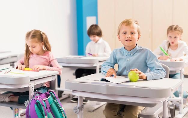 Niños de vista frontal prestando atención en clase.