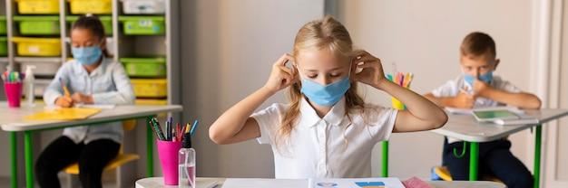 Niños de vista frontal protegiéndose con máscaras médicas