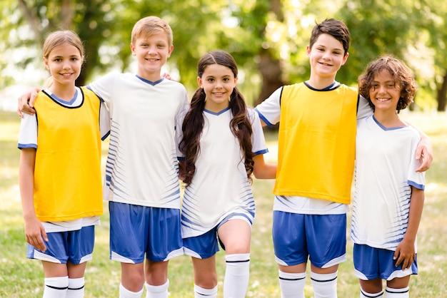 Niños de vista frontal en ropa deportiva de fútbol abrazados