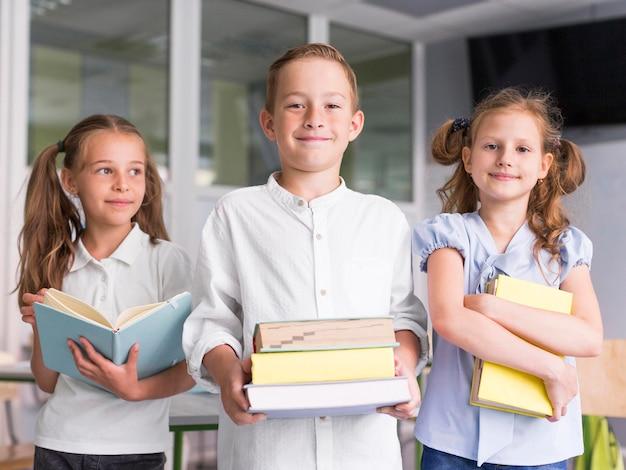 Niños de vista frontal sosteniendo libros en clase