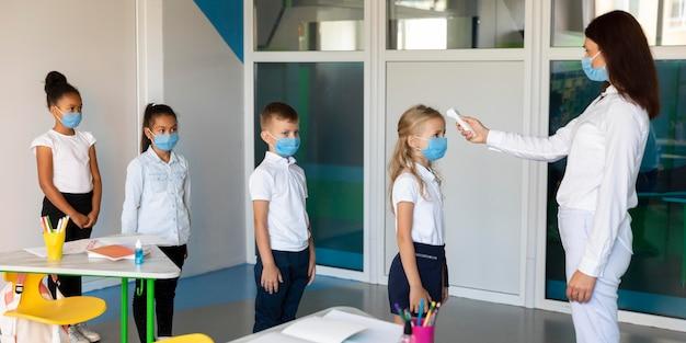 Niños de vista lateral esperando en línea para mediciones de temperatura